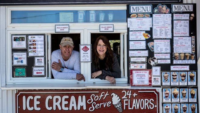 Husband and wife duo, Gary and Karen Bocock, peak out of the serving windows of the Dairy Hut in Pataskala which just opened for the season. The are locally know and famous for their coney dogs and ice cream products.