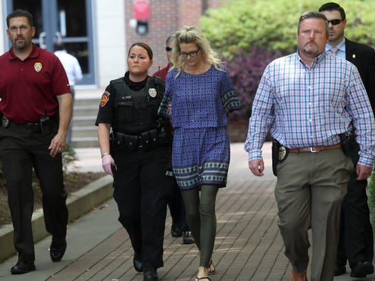 Denise Merrell Williams, 48, is led out of her accounting