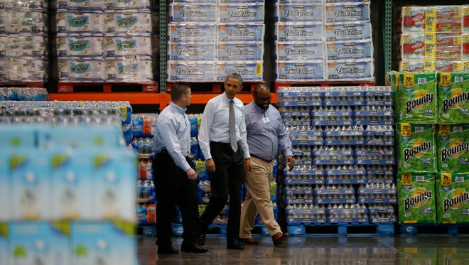 President Barack Obama walks with Ricky Banner, Assistant General Manager, right, and Emile (Ray) Quevedo, floor employee, at a Costco store in Lanham, Md., before he spoke about raising the minimum wage the morning after his State of the Union at the Capitol in Washington, Wednesday, Jan. 29, 2014. President Barack Obama is promoting his newly unveiled plans to boost wages for some workers and help Americans save for retirement _ no action from Congress necessary. (AP Photo/Charles Dharapak)