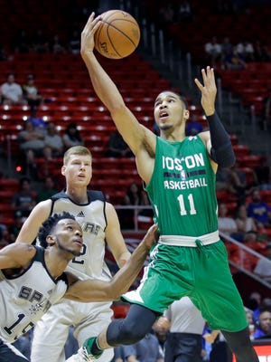 Jayson Tatum lays the ball up as San Antonio Spurs forward Jaron Blossomgame defends during the first half of an NBA summer league game.
