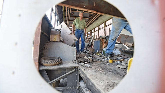 July 9, 2018 Scott Schaut walks through debris in the 1947 bus that once served the Mansfield area as bus No. 60. It was moved Monday morning to the RCT garage. Local historians hope to get donations to restore the bus and keep it in the area.