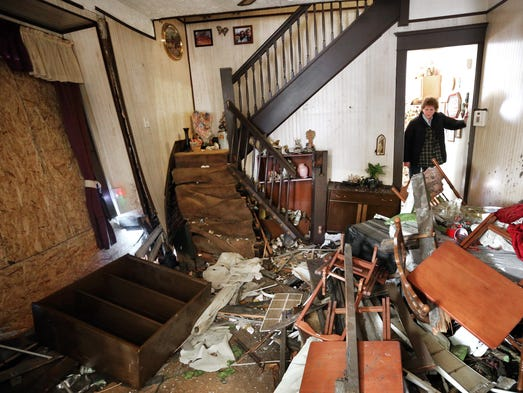 Leigh McCall looks into her living room that was destroyed by a car that flew into her house Sunday, December 29, 2013. Leigh McCall and her husband Tim have lived in the home for the past 30 years and have had 11 accidents of cars into their home over that time span.