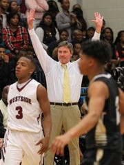 Hanna head coach Barney Brown, middle, celebrates near Westside sophomore Traye Carson, left, and Hanna sophomore guard Issiah Norris, right, as time expires during the fourth quarter on Friday at Westside High School in Anderson. T.L. Hanna won 73-60.