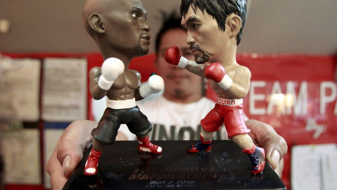 A store employee holds up a stand with miniature figurines of boxers Manny Pacquiao and Floyd Mayweather at a mall in Manila. (Photo: Romeo Ranoco, Reuters)