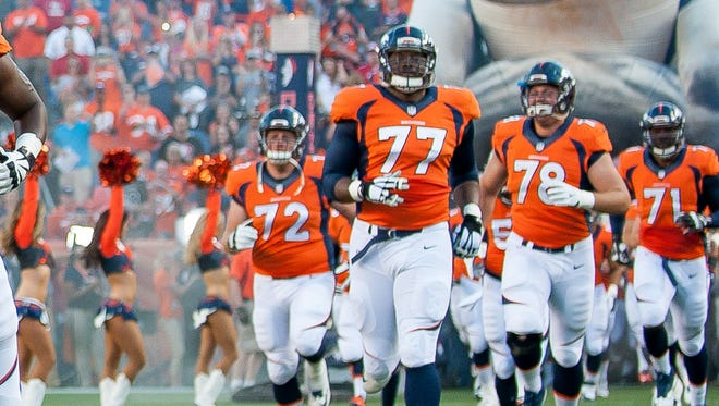 Lars Hanson (No. 78) is among a horde of Broncos running out on the field before a preseason game.
