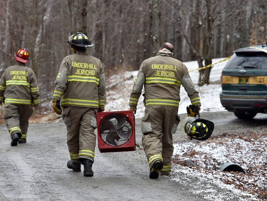 Firefighters carry a fan as rescue personnel and Vermont