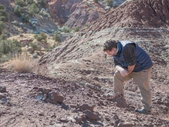 Paleontologist Rob Gay looks over an exposure of Triassic