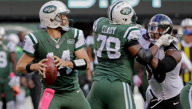 New York Jets quarterback Ryan Fitzpatrick (14) steps back to pass against the Baltimore Ravens during the fourth quarter Sunday.