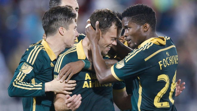 Portland Timbers midfielder Jack Jewsbury, center, is congratulated by defender Jorge Villafana, left, and midfielder George Fochive after Jewsbury scored the winning goal against the Colorado Rapids during the second half of a MLS soccer match in Commerce City, Colo., Saturday, May 30. 2015. Portland won 2-1.