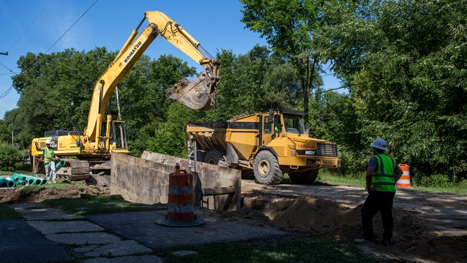 Contactors load a truck with soil as they work on a new sewer line Friday, July 22, 2016 on Main Street in Smiths Creek. Soil from the project is being used to construct a new sledding hill at Smiths Creek Community Park on Henry Street.