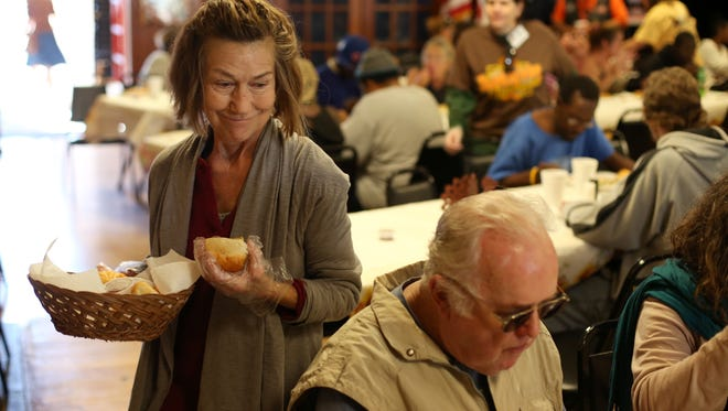Volunteer Robin Sparks passes out food during a community Thanksgiving celebration at American Legion Hall Post 13 last year.