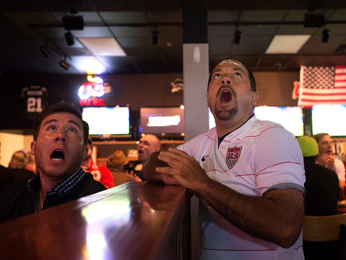 Tyler Campos, left, and Mike Scimeca watch the World Cup United States versus Belgium match at Ryan's Sports Grill in Fort Collins Tuesday, July 1, 2014.