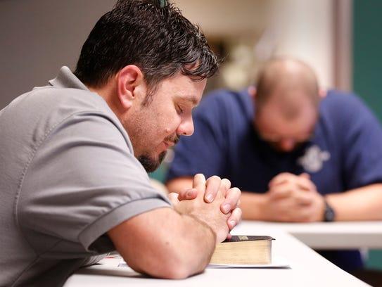 Adam Winn joins men in prayer after reading portions