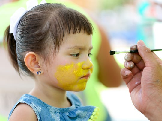 """Aubrey Marez, 3, of Las Cruces, keeps her eyes on the paint brush as they gets her face painted as a """"Minon"""" on Saturday July 29, 2017 during the Kids EXPO 2017 at the Plaza de Las Cruces. The annual family event was free and open to all ages."""