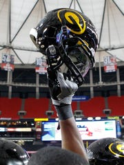 A Grambling State Tigers player raises his helmet.