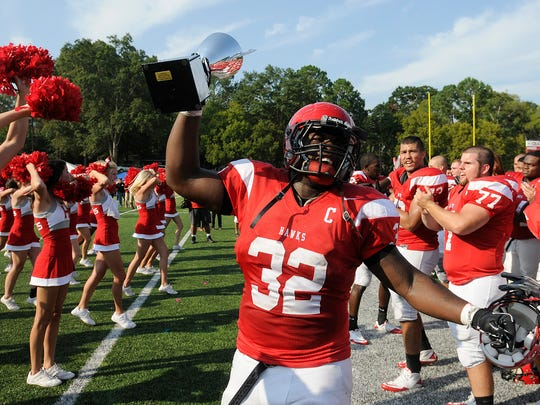 Huntingdon linebacker Kirk Johnson hoists the trophy for the Capital City Showdown as Huntingdon College players celebrate at the end of their game with Faulkner University at Huntingdon Saturday, Sept. 17, 2011. Huntingdon won 48-41. David Bundy/Special to the Advertiser