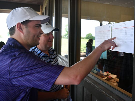 Michael Stevenson, left, and Keith Pistocco check their tee assignments at the 31st Annual Friends of Hospice Golf Tournament Monday morning at the Wichita Falls Country Club. More than 50 teams participated in this year's fundraiser.