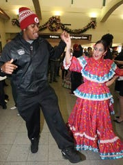 Washington State linebacker Ivan McLennan learns a few folklorico steps while dancing with Rebecca Vargas of Nuevo Amanecer dance group upon the team's arrival at the El Paso Airport on Monday night. The Washington State Cougars will play the Miami Hurricanes in the 82nd Hyundai Sun Bowl game on Saturday.