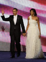 This Jan. 20, 2009 photo shows President Barack Obama, left, and first lady Michelle Obama, in a one-shouldered white gown by designer Jason Wu, at the Neighborhood Inaugural Ball in Washington.