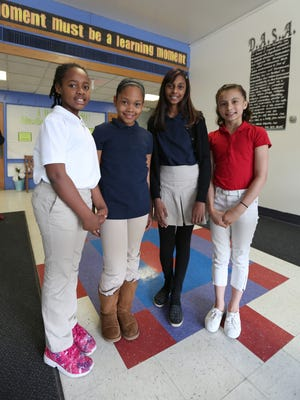 Lime Kiln fifth-graders Jovanie Williams, left, Shaniah Smith, Alisha Charles and Madison Vale show off the uniforms that would be worn at the school. A magnet school is being planned for next year at the school.