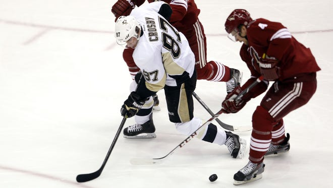 Sydney Crosby of the Penguins is surrounded by Oliver Ekman-Larsson (23) and Zybnek Michalek (4) of the Coyotes  during the first period of an NHL hockey game Saturday, February 1, 2014, at Jobing.com Arena in Glendale.