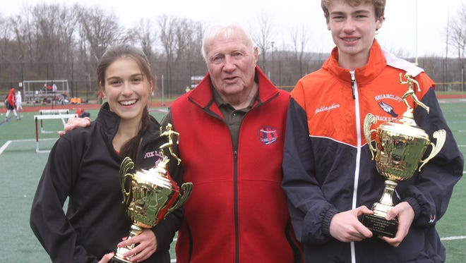 From left, Fox Lane's Vicky Martinez and Briarcliff's Ryan Gallagher stand with John Covert after they won the John Covert  Mile during the annual Ossining Relays in Ossining April 9, 2016.