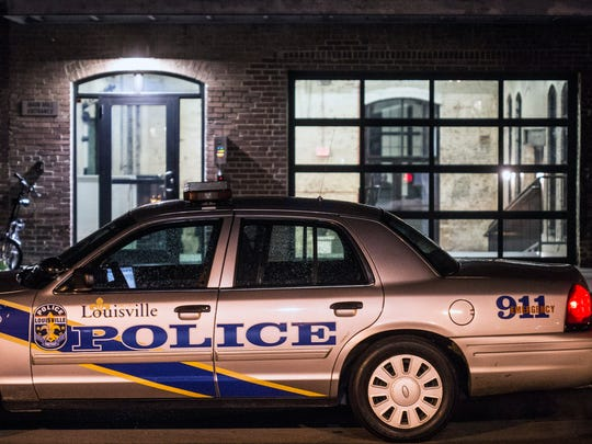 Police cruisers are parked near the rear entrance of