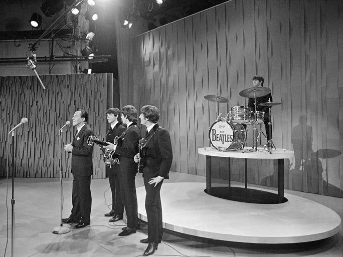 "Ed Sullivan announces The Beatles during their first appearance on ""The Ed Sullivan Show"" on Feb. 9, 1964. Ed Sullivan, left, Paul McCartney, George Harrison, John Lennon and Ringo Starr share the stage."