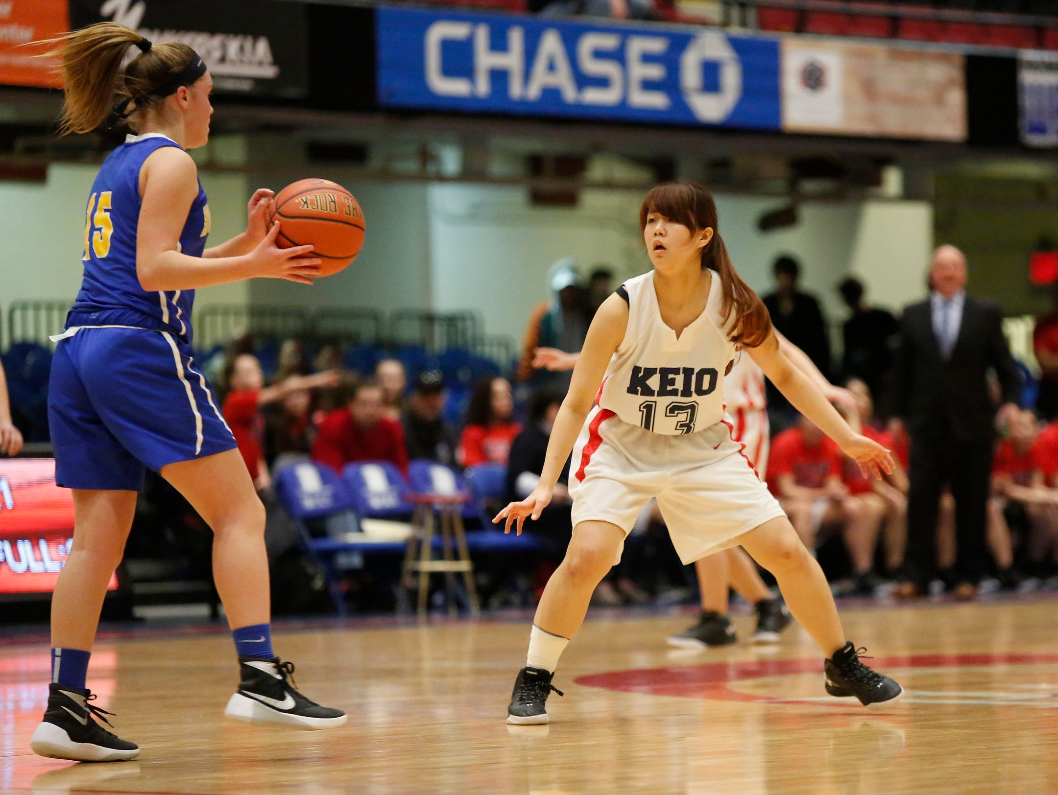 Keio's Mako Morozumi plays a tough defense on North Salem's Geace Curren (15) in the class C semi-final basketball game at the Westchester County Center in White Plains on Saturday, February 27, 2016.