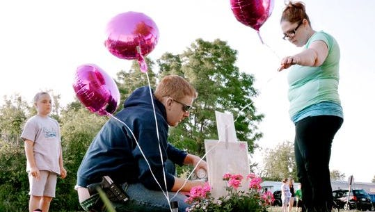 Christopher Gift and his fianceé, Carrie Kaziska, along with Gift's children, leave balloons and a candle by a memorial for 3-year-old homicide victim Isabel Rose Godfrey. (Randy Flaum photo)