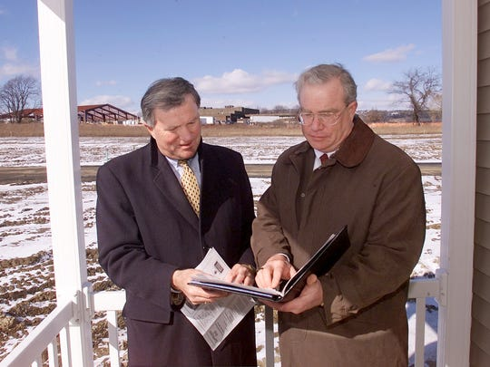 Developers Clay Ambrose, left, and his brother Art review plans on the porch of a home being built at Barrington West in Horseheads in 2002.