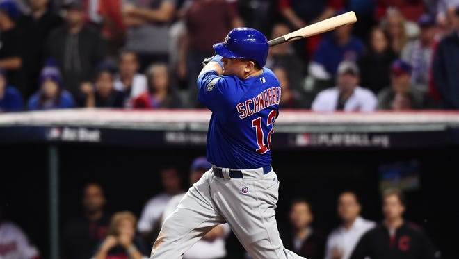 Chicago Cubs player Kyle Schwarber (12) hits a single against the Cleveland Indians in the 10th inning in game seven of the 2016 World Series at Progressive Field.
