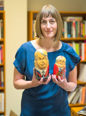 Pictured is Dr. Allison Evans holding matryoshka dolls, otherwise known as Russian nesting dolls, depicting Russian President Boris Yeltsin and Soviet President Mikhail Gorbachev.