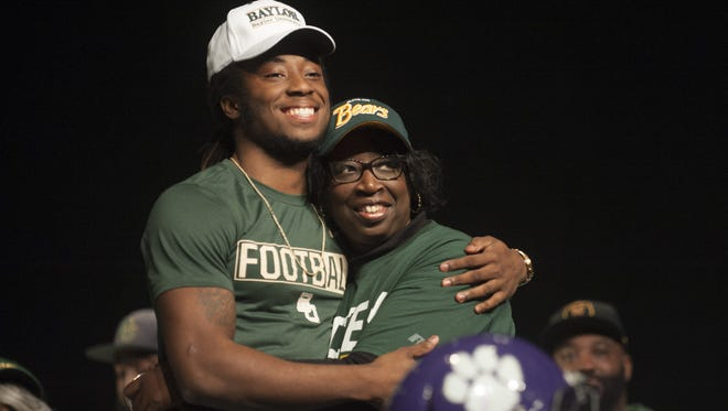 Cherry Hill West senior Harrison Hand gets a hug from his mother, Denise Hand, after signing his National Letter on Intent on Wednesday to attend Baylor University.