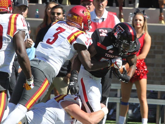 Texas Tech Red Raiders running back Tre Walker (24) is tackled by Iowa State Cyclones strong safety Reggie Wilkerson (3) at Jones AT&T Stadium.