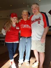 Patty Irving (left), Jerry Kratz and Bob Cowden, members of the Capri Christian Church, show off their baseball team preferences by wearing team paraphernalia.