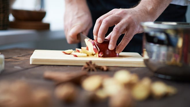 Hands of chef slicing an apple