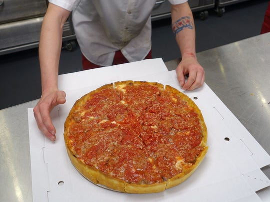 A cook at Lou Malnati's in Phoenix slices a pizza for