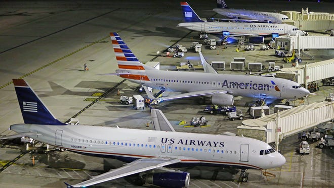 An American flight arrives at US Airways gate B6 during American Airlines' overnight move from Terminal 3 to Terminal 4 Tuesday, Feb. 25, 2014 at Phoenix Sky Harbor International Airport.