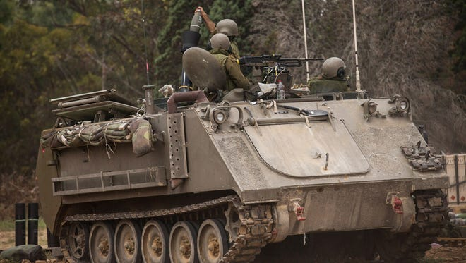 Israeli soldiers fire mortars from an armored personnel carrier near the Israeli-Gaza border near Sderot, Israel, on July 21.