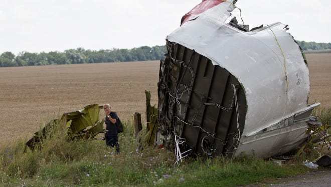 A Malaysian air crash investigator examines wreckage at the crash site of Malaysia Airlines Flight 17 near the village of Hrabove, eastern Ukraine, on Tuesday.