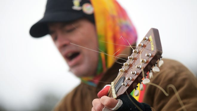 Jonathan Chase Melzer sings as he plays his guitar on U.S. Route 13 in Onley, Va. near the Walmart store in 2015.