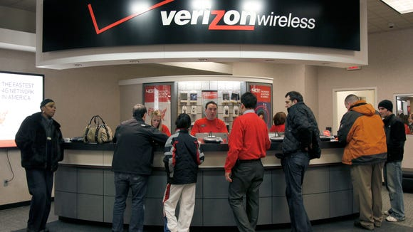 File photo taken in 2011 shows cell phone customers at the counter of the Verizon store in Beachwood, Ohio.