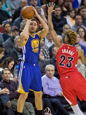 Golden State Warriors guard Klay Thompson (11) shoots a three point basket over Portland Trail Blazers forward Allen Crabbe (23) during the first quarter at the Moda Center.