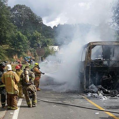 Unos bomberos apagan el fuego de un autobús de pasajeros, este 27 de septiembre de 2016, que fue incendiado durante un enfrentamiento registrado en el municipio mexicano de Chilchota entre policías estatales y alumnos de la Escuela Normal Indígena de Cherán, formadora de maestros de educación básica; que dejó un saldo de 49 estudiantes detenidos.