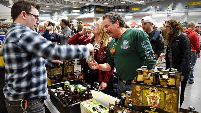 Scott Ketcher, Founders Brewing Co., serves samples to Carol Stice and her husband, Dave Shore, Monticello, during the St. Cloud Craft Beer Tour on Saturday, Jan. 16, at the River's Edge Convention Center.
