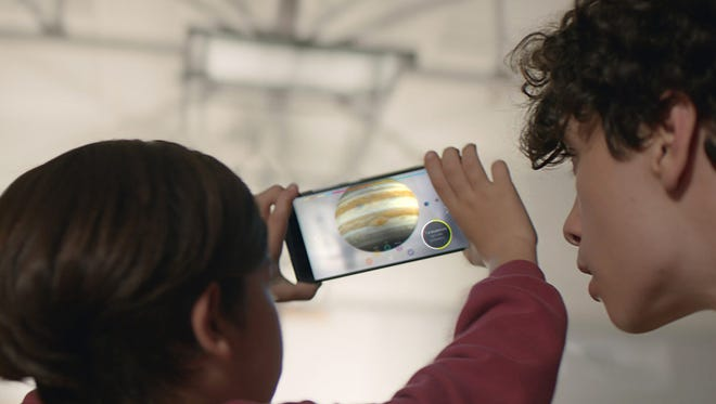 """This image provided by Google shows people looking at a view of the solar system using technology Google calls """"Project Tango."""""""