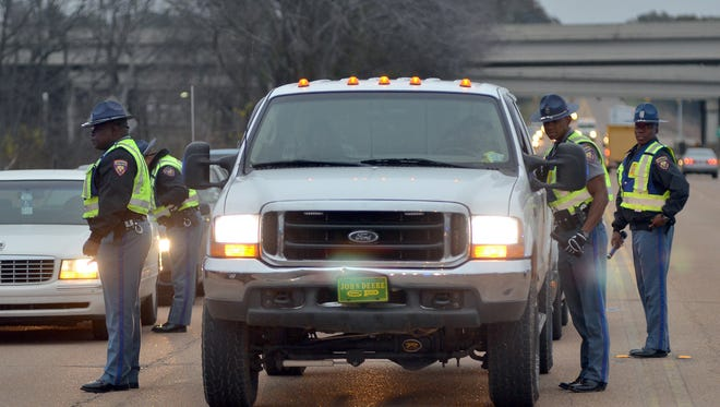 Mississippi Highway Safety Patrol troopers check the license and paperwork of a motorists Friday during a road block along U.S. 80 at the Pearl River bridge in Rankin County.