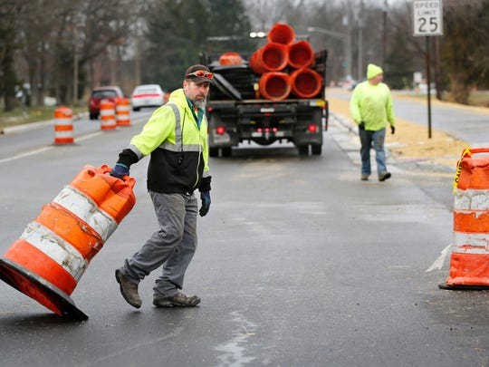 Sean Ledman, foreground, and Taylor Bray remove traffic barrels as Happy Hollow Road is prepared to open for two way traffic Friday, December 23, 2016, in West Lafayette. Both of the men work for Highway Safety Services.