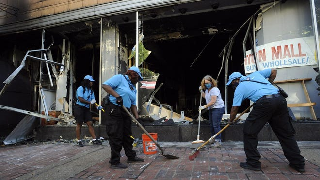 Workers and a volunteer clean up damage outside a burned-out clothing store in Birmingham, Ala., on Monday, June 1, 2020, following a night of unrest. People shattered windows, set fires and damaged monuments in a downtown park after a protest against the death of George Floyd. Floyd died after being restrained by Minneapolis police officers on May 25.